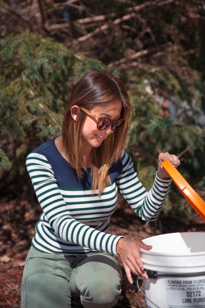 Jenny checking sap bucket with lifted optics